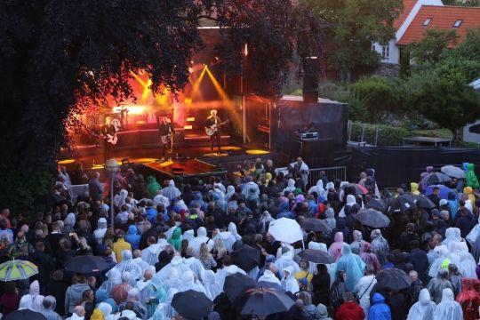 Koncert med regntøj og paraplyer